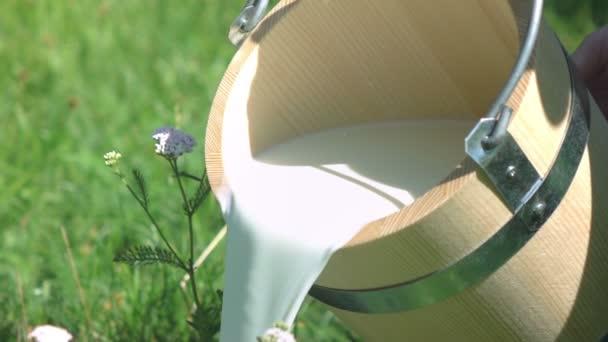 Dvě videa lití mléka z dřevěné vědro skutečné zpomalené