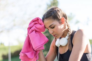 Young sports woman resting and wiping her sweat with a towel.