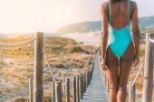 schöne junge schwarze Frau in einer hölzernen Fußgängerbrücke am Strand
