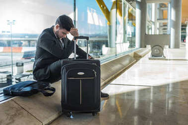 young businessman angry at the airport waiting his delayed flight with luggage