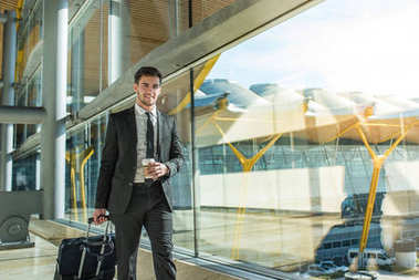 young businessman walking at the airport terminal with luggage smiling with a coffee