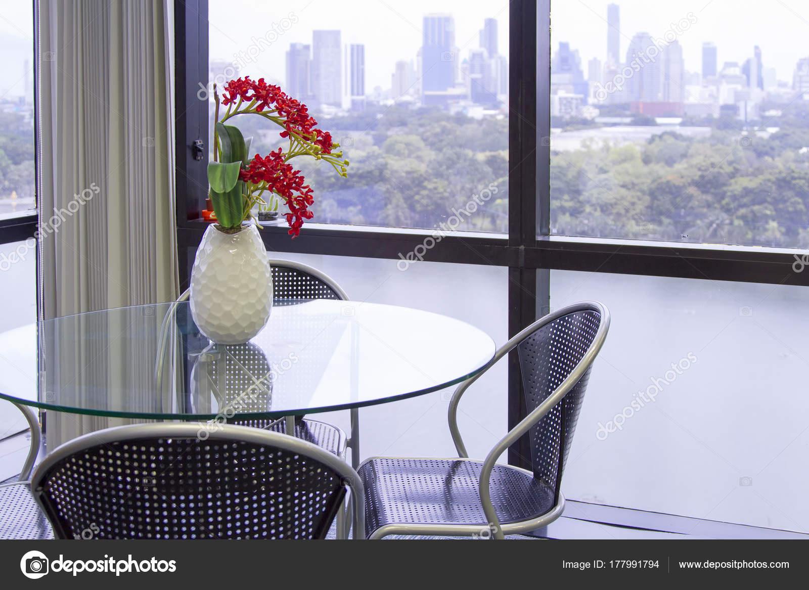 Runder Glastisch mit schwarzen Stuhl mit weißen Vase, rote Blume o ...