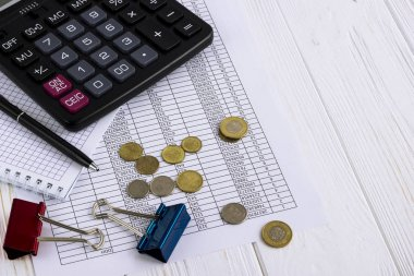 calculator, coins, pen, office accessoriesand financial paper on