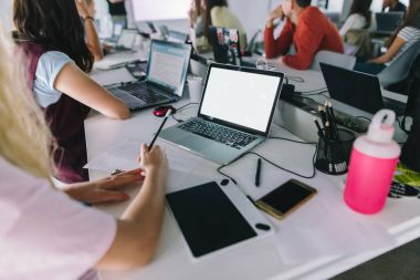 A notebook with a white screen in focus. A group of people sitting at a desk with laptops and notebooks and studying. A group of employees are sitting in the office and working.