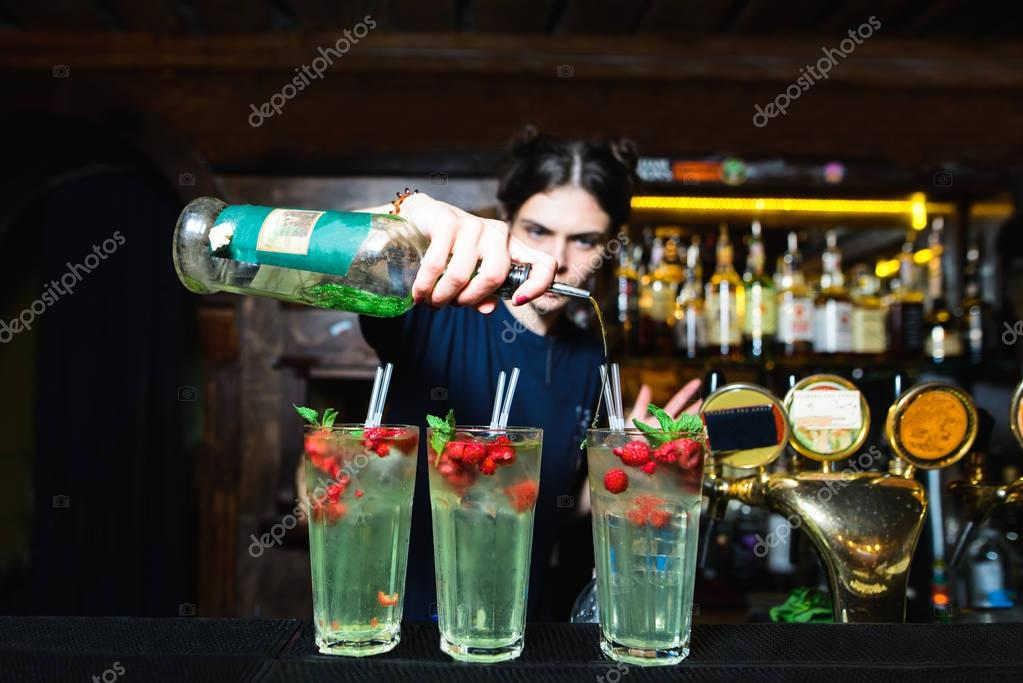 A bartender girl creates beautiful alcoholic cocktails with berries in a nightclub. The barman drinks bottled alcohol in a cocktail.