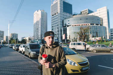 Street portrait of a young man with a backpack and a cup of coffee in hand against cars and architecture. A man is waiting for a taxi near the road.