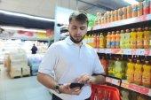 Fényképek Egy ember, egy kosár, úgy néz ki a telefon egy szupermarketben vásárlás közben. Vásárolni a boltban. a közelében az italokat a szupermarketben