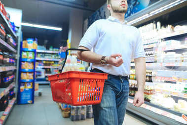 A man with a red shopping basket strolls around the supermarket. A man buys goods in a supermarket.