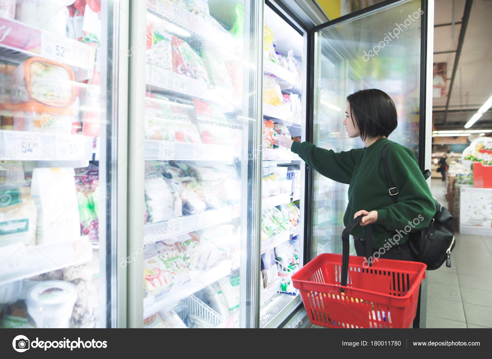 Kühlschrank Korb : Ein mädchen mit einem korb nimmt gefrorene lebensmittel aus dem