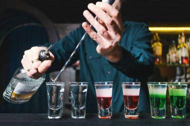 barman pouring alcoholic shots at bar counter at restaurant