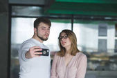 Beautiful couple man and woman doing selfie office. Office workers are photographed on the phone
