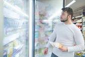 Fényképek Portréja egy ember közelében egy hűtőszekrény, egy szupermarket fagyasztott élelmiszerek a kezében. Egy szupermarket termékek megvásárlása