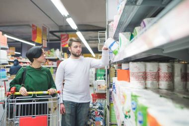 A beautiful couple buys household goods for home in the store. Family shopping at a supermarket