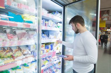 A man chooses frozen foods from shelves in a refrigerator in a supermarket. A man buys products in the store. Shopping in a supermarket concept.