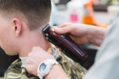 Fotografie Haircuts in barbershop. The hairdresser shaves a young man hair clipper. Mens haircuts in the beauty salon.