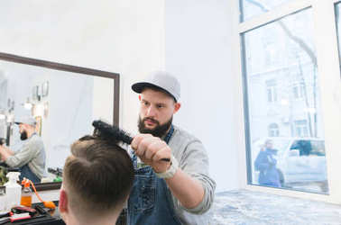 A stylish male hairdresser makes a man's hairstyle in a beauty salon. Stylish haircut in barbershop.