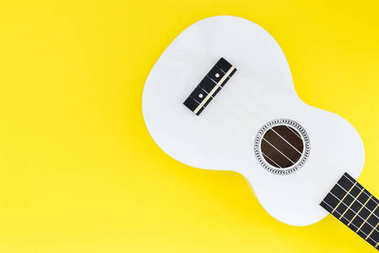 White ukulele on a yellow background and with a place for text. Musical concept.