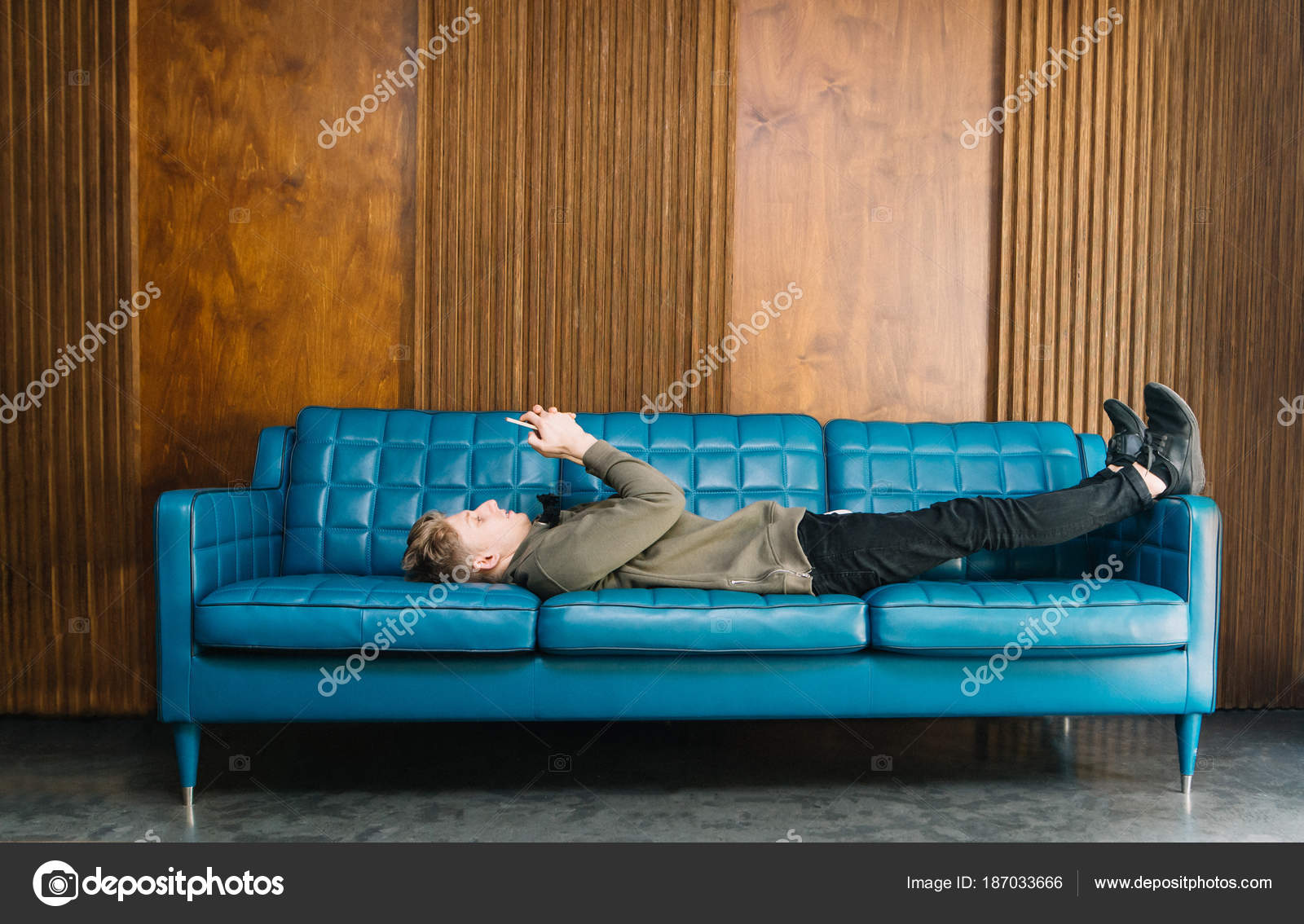 Superb A Young Man Lays On A Stylish Blue Sofa And Uses A Inzonedesignstudio Interior Chair Design Inzonedesignstudiocom