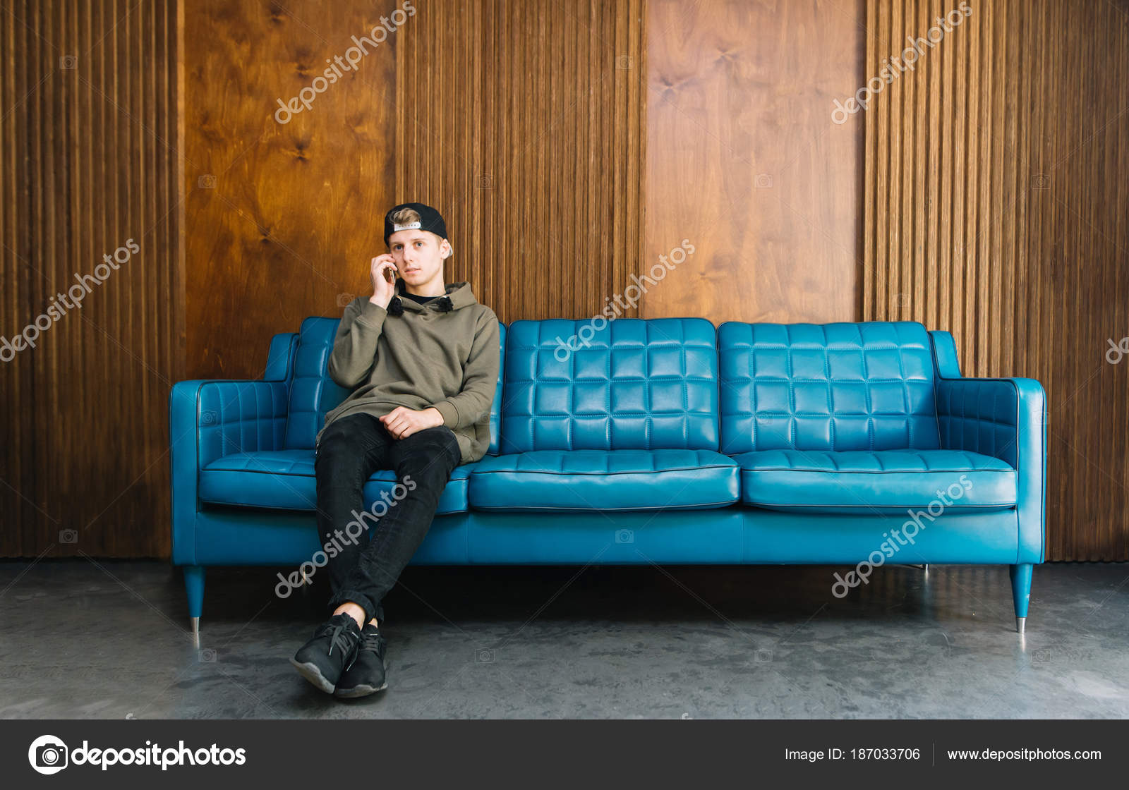 Prime Young Man Sitting On A Blue Sofa And Talking On The Phone A Inzonedesignstudio Interior Chair Design Inzonedesignstudiocom