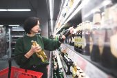 Fényképek Egy gyönyörű lány vesz alkoholos italok a szupermarket polcain való helybiztosítást. Az alkohol a boltban vásárlás
