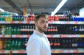 Fényképek Hátterében a frissítő italokat a szupermarketben egy fiatal férfi portréja
