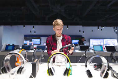 Young man looks at headphones in the electronics store Choosing