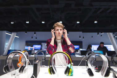 The buyer evaluates the sound of the headphones. A young, handso