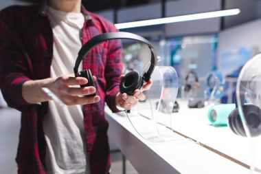 A man holds black headphones in the background of the store. Buying headphones in a tech store.