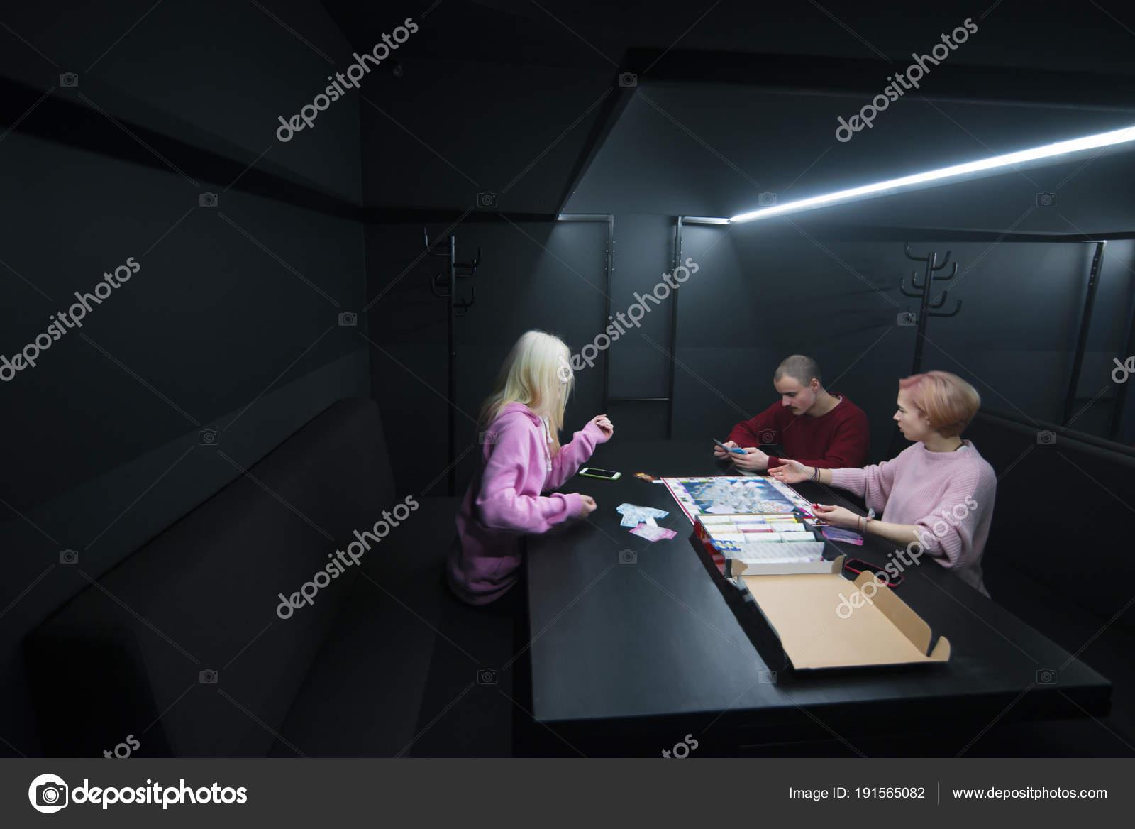 Unga människor sitter vid bordet i ett mörkt rum 109edce184257