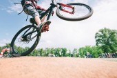 Fotografie Tricks on the bike. A young man jumps on a mountain bike. Cycling Sports Concept.