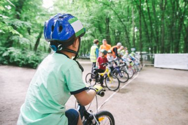 Children's cycling. Boy in a helmet against background of cyclists who are at the start. Children's sports