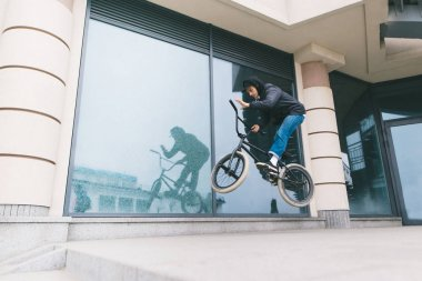 A young man is doing tricks on BMX against the backdrop of architecture. A boy jumps on a BMX bike