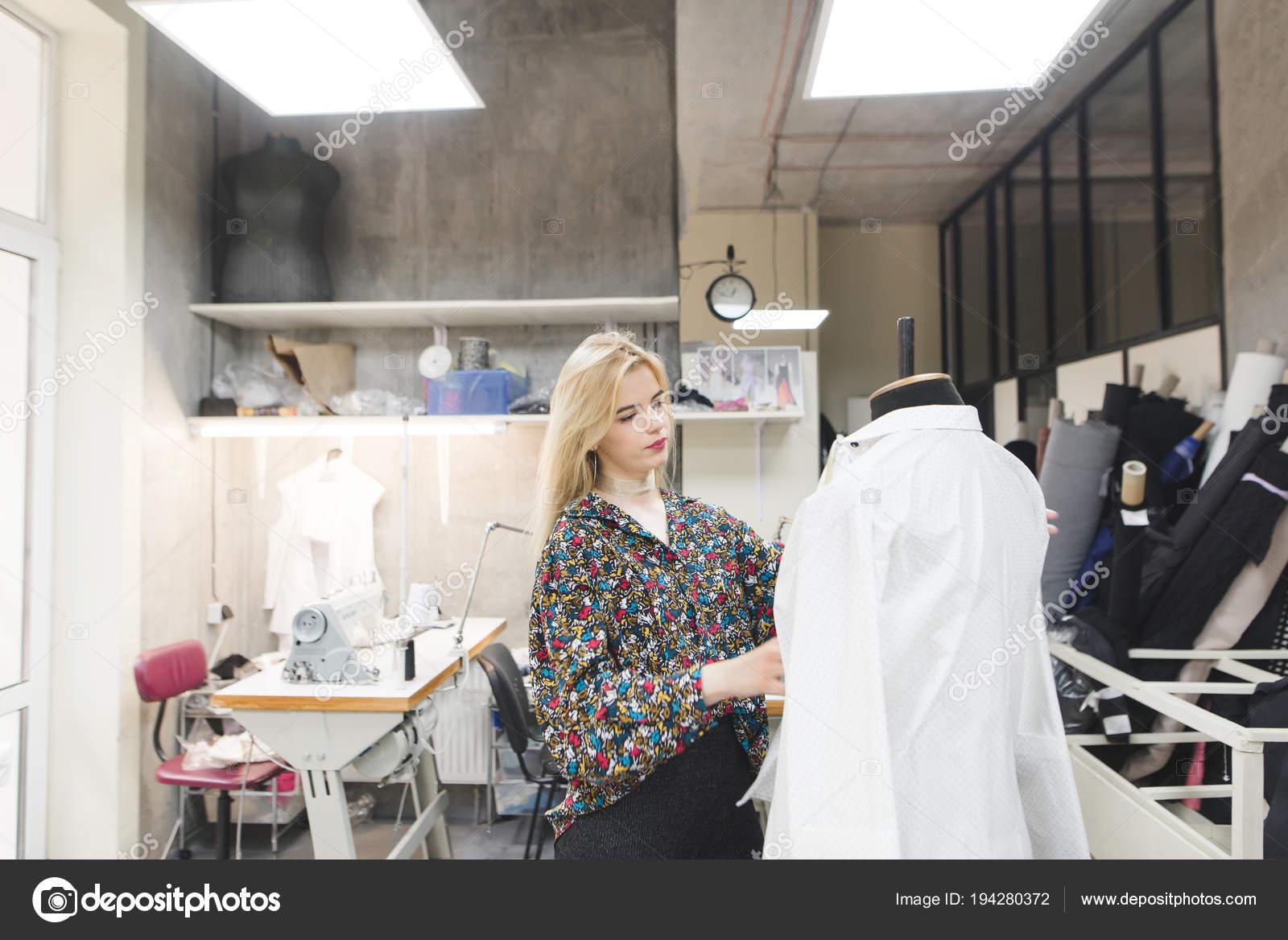 81dca5a27b635 Designer de moda jovem de pé no estúdio e experimentando roupas em um  manequim. Criação de roupas de moda. O designer cria roupas elegantes —  Foto de ...
