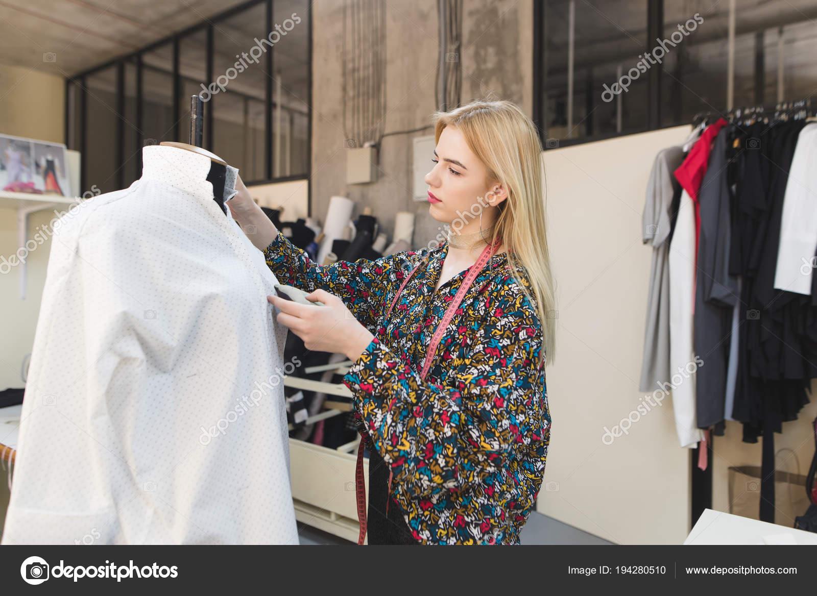 7700fb0939200 Um jovem designer de moda cria roupas em um estúdio de moda. Costureira  feminina jovem está em um estúdio bem cuidado e ajusta roupas — Fotografia  por ...