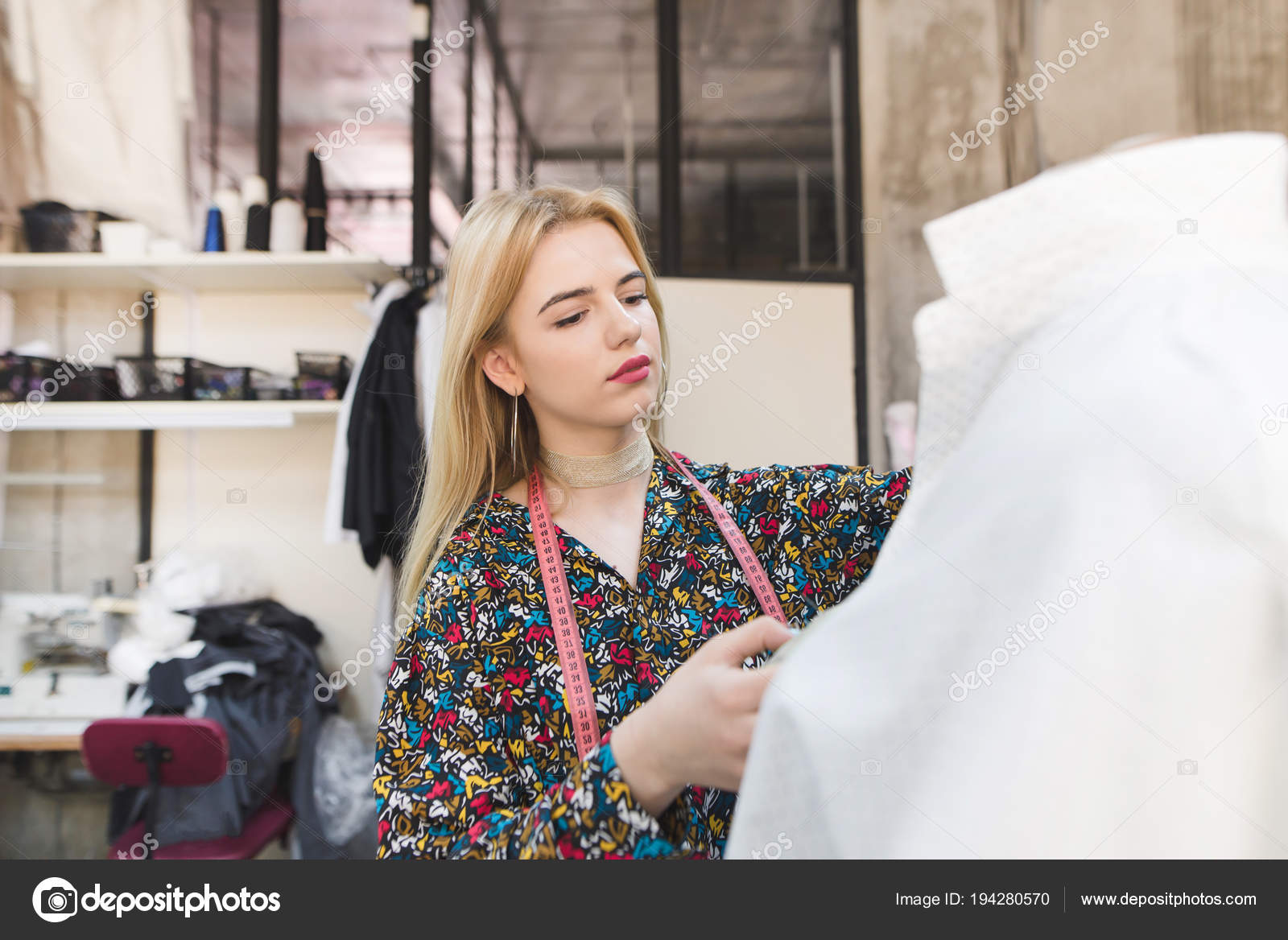 defbeb2ad1555 Retrato de jovem designer shane e trabalho em seu próprio estúdio de moda.  A linda garota está aguardando o boneco com roupas e trabalhando.
