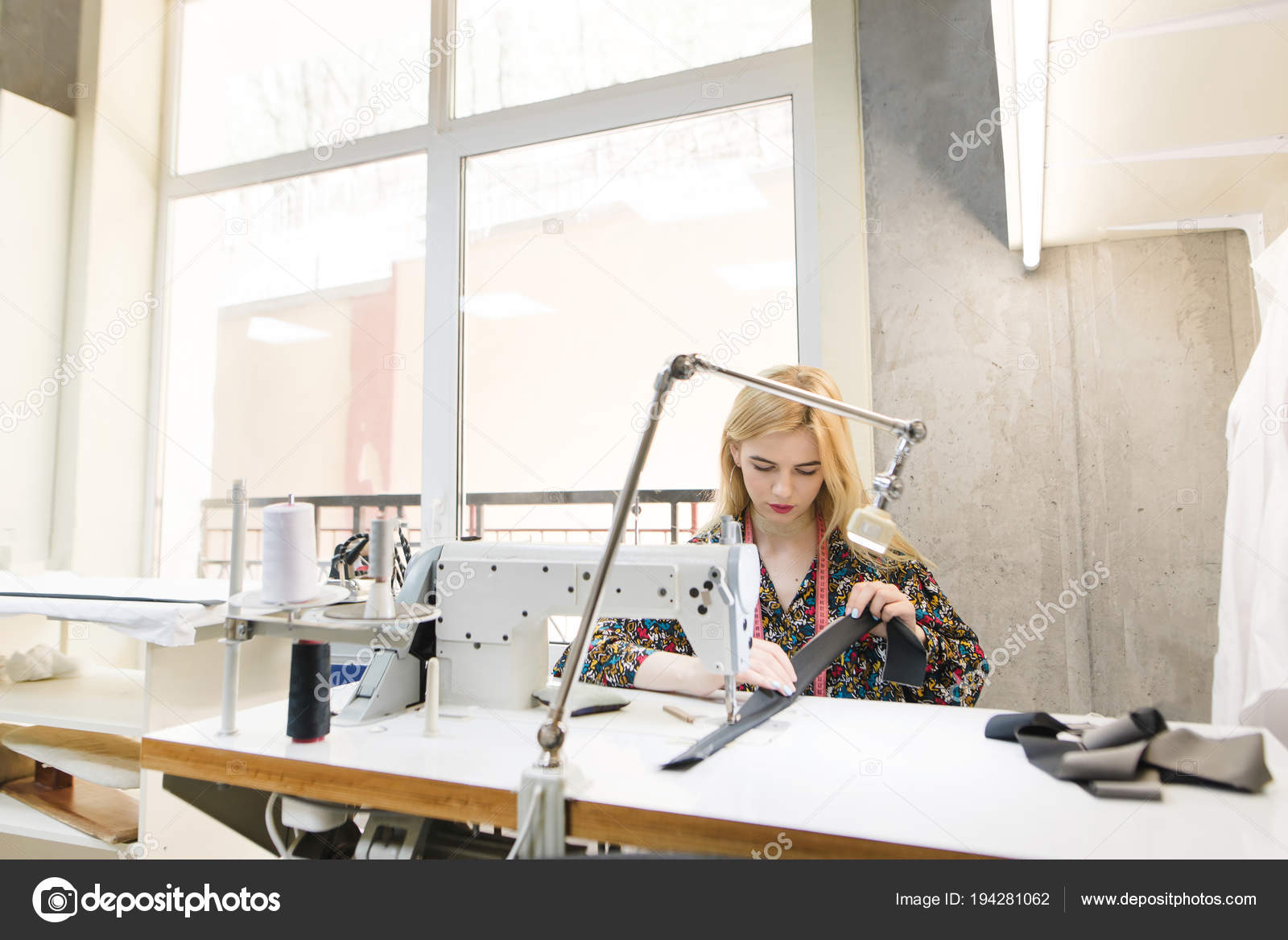 Portrait Of A Cute Young Seamstress At Work On A Professional Sewing