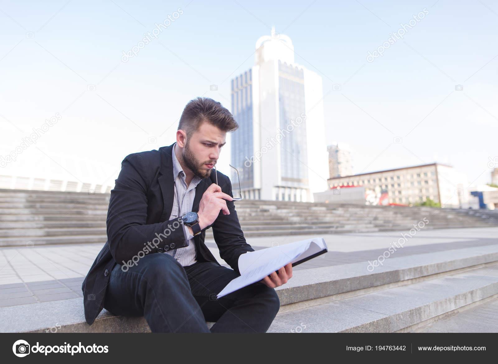 f01202897966 Concentré d homme dans un costume d affaires assis sur les marches et la  lecture des documents qui tient dans ses mains. Un homme d affaires grave  se penche ...