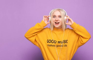 Emotional girl in a street casual clothing and headphones standing on a purple background with astonished face looking into the camera. Expressive teen girl listens to music in headphones, isolated.