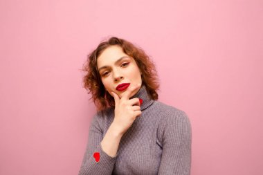 Closeup portrait of pensive girl in casual clothes and with makeup isolated on pink background,looking at camera and thinking. Smart lady with curly red hair on a pink background, looking thoughtfully