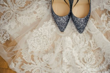 beautiful stylish gray high-heeled shoes from a famous brand are standing in a white laced veil