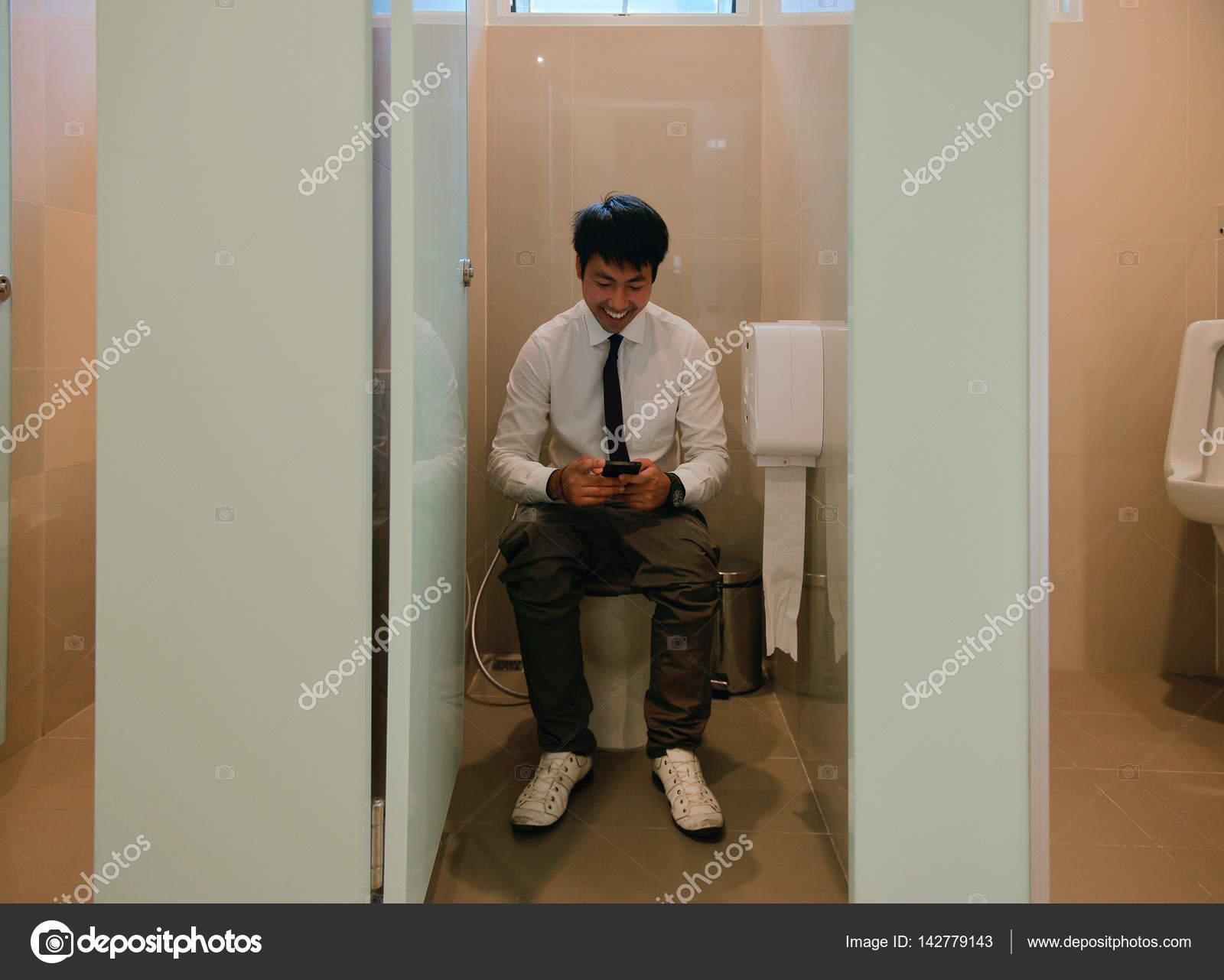 Un Homme D Affaires Asiatique Caca Et En Utilisant Le Smartphone