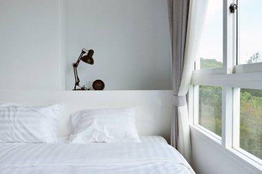 modern lamp on wooden nightstand in white modern bedroom, interi