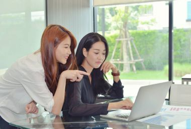 Asian business women discussing with each other