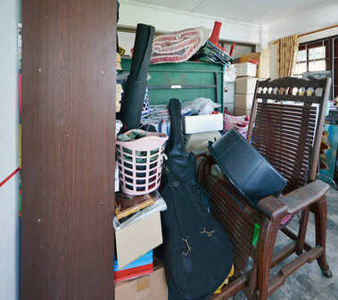 Messy storage room in garage for junk in old house