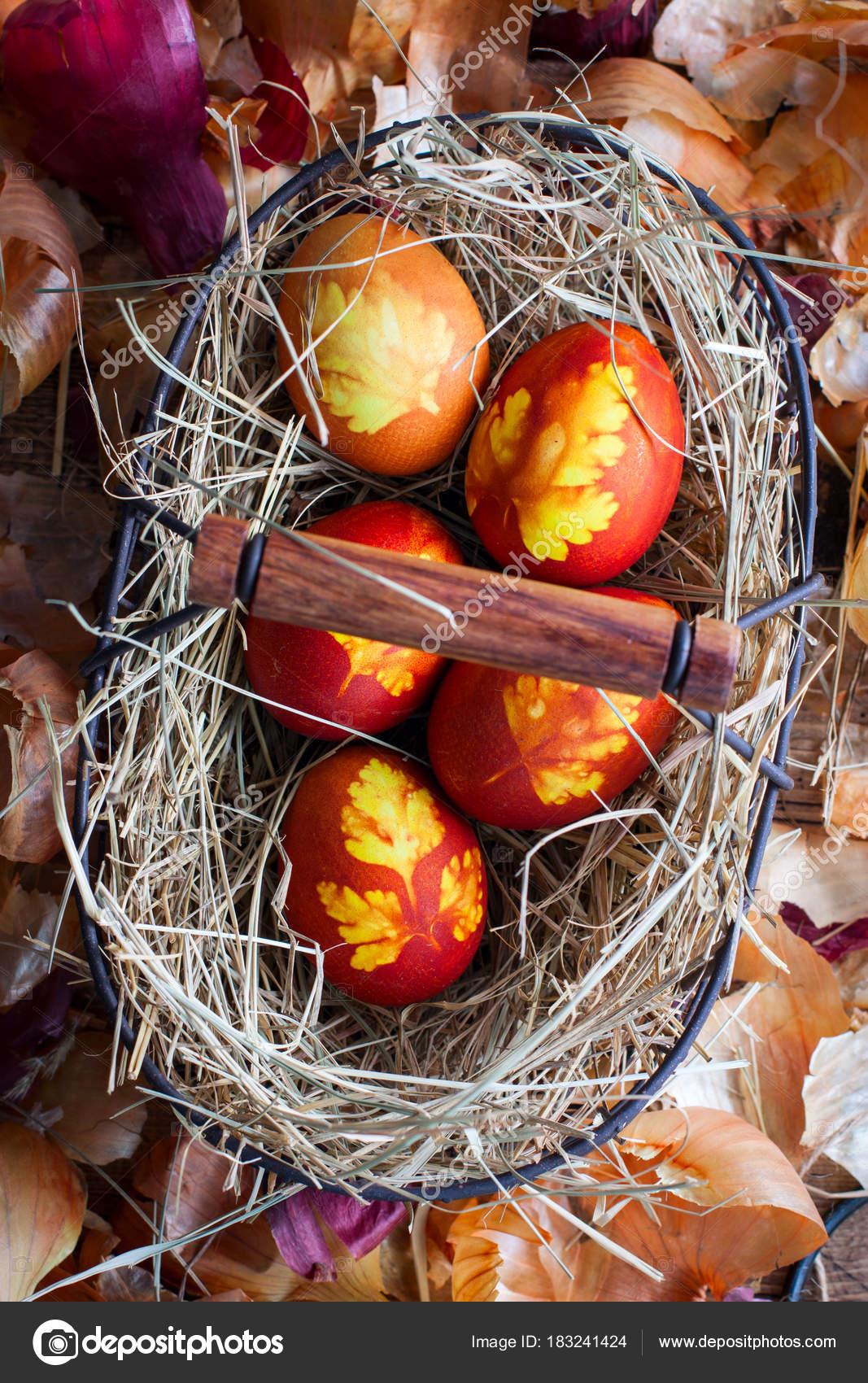 Pintar huevos de Pascua con un patrón de hojas en una cesta metálica ...