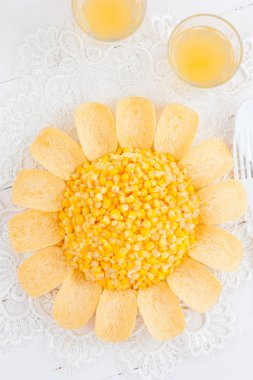 Salad in the shape of a yellow sun with chips and corn on a white table, top view, selective focus