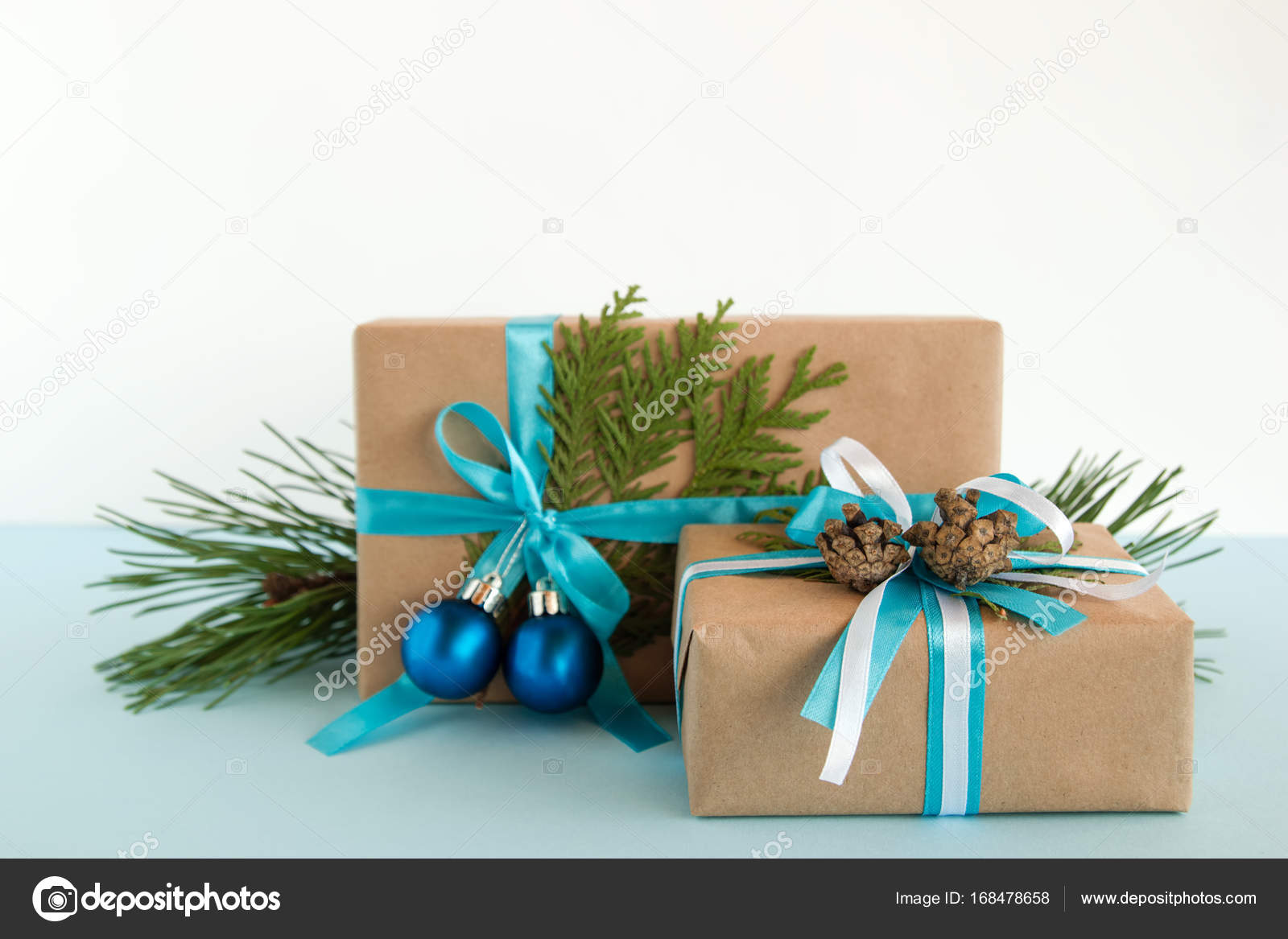 christmas gift boxes wrapped of craft paper blue and white ribbons decorated of fir branches pine cones and christmas balls on the blue and white