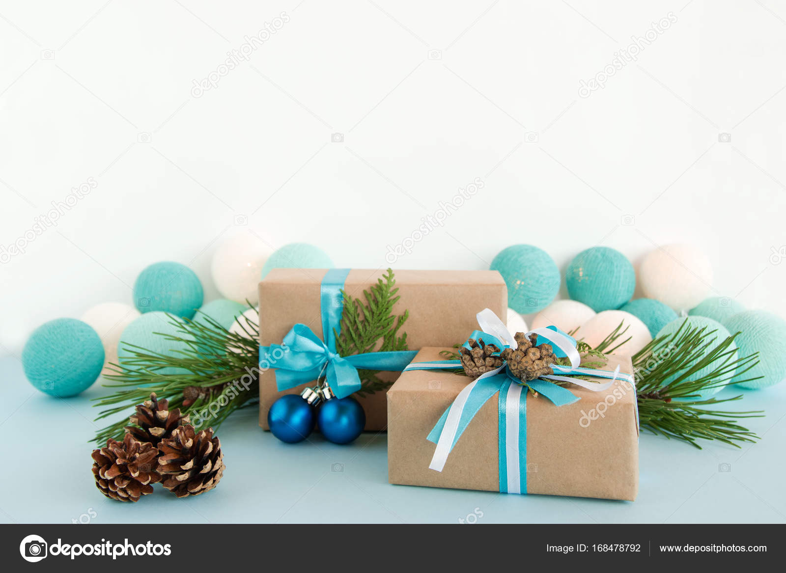 Two Christmas t boxes wrapped of craft paper blue and white ribbons decorated of fir branches pine cones and Christmas balls on the blue and