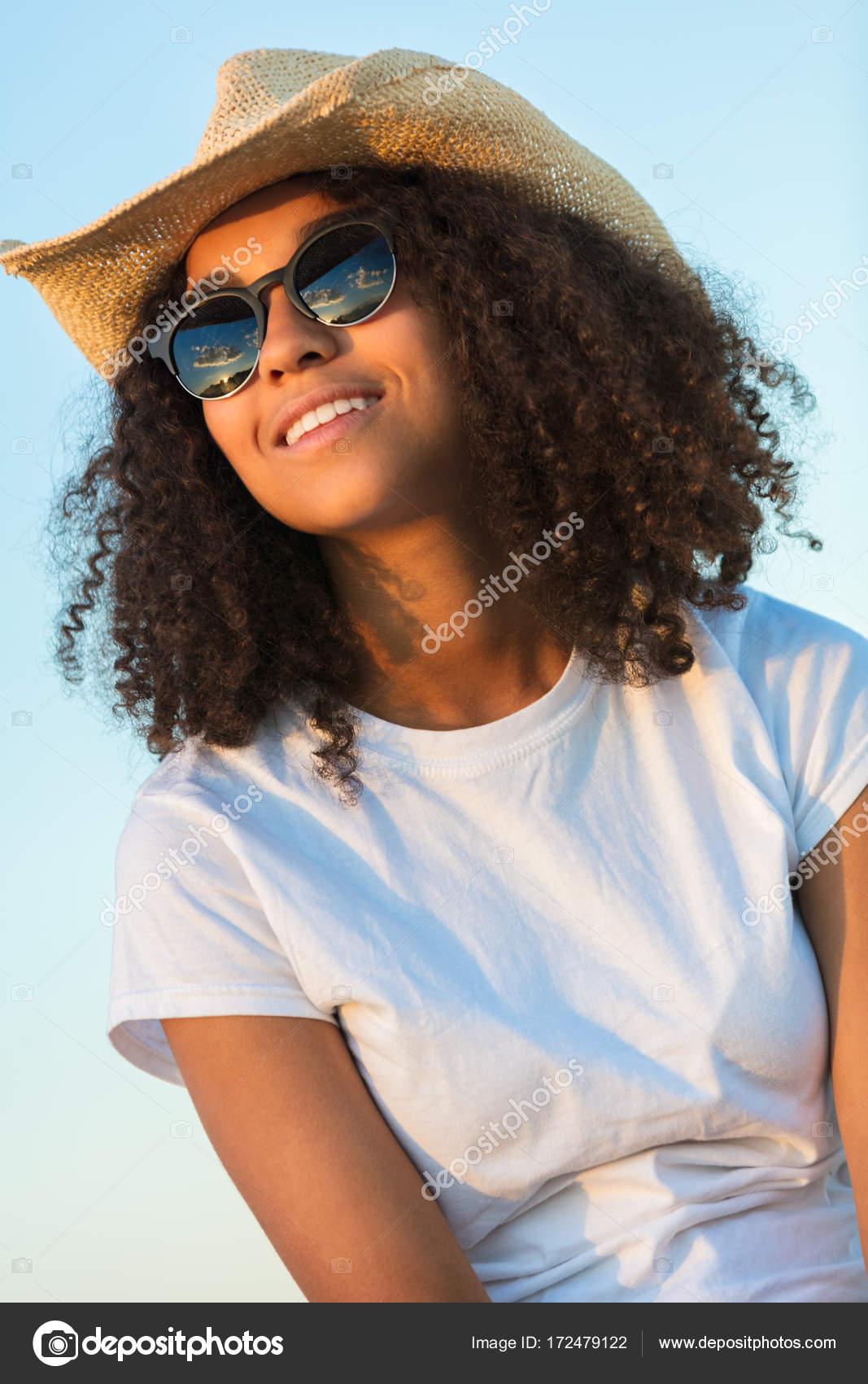 Bella feliz mestizaje americano africano mujer niña adolescente joven  usando relective aviador gafas de sol y sombrero de vaquero fuera en oro  del atardecer ... 96ec40134d3