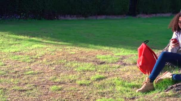 329ee18e08 Panoramique de 4k clip vidéo des belles heureux mélangé adolescent fille  afro-américaine de course assis par un arbre avec un sac à dos rouge et à  l'aide ...
